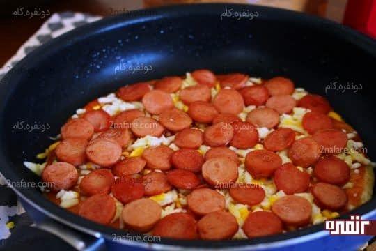 قرار دادن پپرونی های سرخ شده روی لایه از پنیر پیتزا